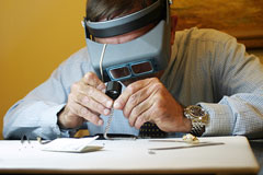 a jeweler, wearing a binocular headband magnifier, examines bracelet diamonds