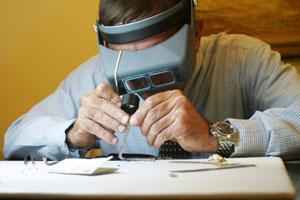 a jeweler, wearing a binocular headband magnifier, examines bracelet diamonds