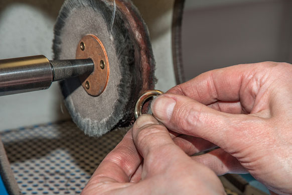 jeweler buffing a golf ring on a buffing machine