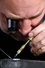 jeweler, wearing an eyepiece magnifier, using a soldering iron to repair a silver ring