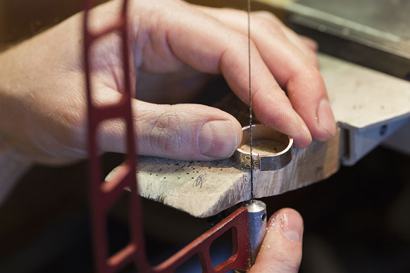 sawing a ring with a jeweler's saw